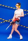 Sexy brunette builder on a blue background with an electric tool in the hands of. Builder woman in sexy clothes on a blue background holding a male construction Royalty Free Stock Photography