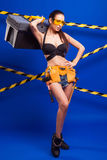 Sexy brunette builder on a blue background with an electric tool in the hands of. Builder woman in sexy clothes on a blue background holding a male construction Stock Photos