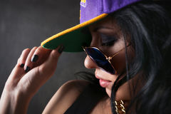 Brunette in a cap covering her eyes. Brunette holding purple cap and closed her eyes stock images