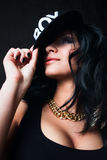 Brunette in cap. Swag. Brunette with beautiful breasts with a gold chain holding cap stock images