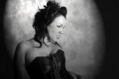 Sexy brunette in corset spotlit. Sexy, busty, brunette in a black corset,spotlit, a seductive black and white image Royalty Free Stock Photography