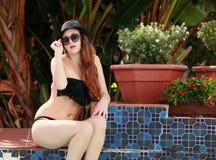 Sexy Brunette-Dame nahe bei dem Swimmingpool Stockfotografie
