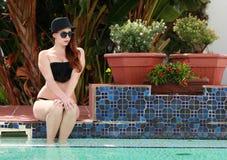 Sexy Brunette-Dame nahe bei dem Swimmingpool Stockbild