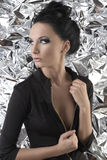 Sexy brunette with dark dress touches the zipper Stock Images