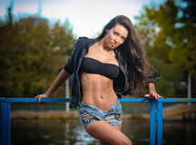 Sexy brunette in denim shorts posing provocatively outdoor. Portrait of a beautiful sexy woman with denim shorts in a park Stock Photography