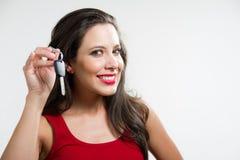 Sexy brunette die een autosleutel houdt Stock Afbeeldingen