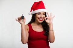 Sexy brunette die een autosleutel houdt, die santahoed draagt Stock Foto's