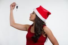 Sexy brunette die een autosleutel houdt, die santahoed draagt Royalty-vrije Stock Foto