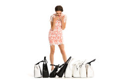 Sexy brunette in dress with necklace and a lot of bags isolated Royalty Free Stock Photography