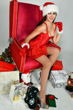 Sexy brunette dressed as Mrs. Santa posing pretty sitting in classical armchair. Christmas decoration Stock Photo