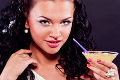 Sexy brunette drinking cocktail. Beautiful woman with curly hair, drinking a cocktail Stock Image