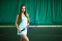 Sexy brunette female tennis player posing on an indoor tennis court Stock Image