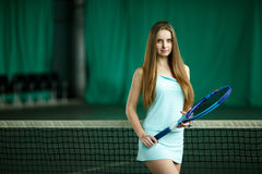 Sexy brunette female tennis player posing on an indoor tennis court Stock Photo