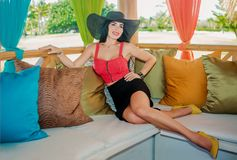 Sexy brunette in the gazebo with cushions. Sexy brunette with long hair and red top on the sofa with cushions in the gazebo Royalty Free Stock Image