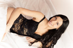 Sexy brunette girl with blue eyes in black lingerie lying on white bed looking at camera smiling portrait image Royalty Free Stock Photo
