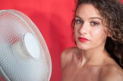 brunette girl with curly hair with cooling fan royalty free stock image