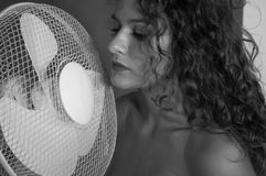 brunette girl with curly hair with cooling fan royalty free stock photo