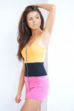 Sexy brunette girl in mini skirt. Posing against white wall Royalty Free Stock Photos
