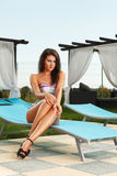 Sexy brunette girl at pool. Beautiful young sexy brunette girl sitting on chair next to a pool Stock Image
