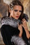Sexy brunette girl posing in luxury elegant fur coat Royalty Free Stock Photos
