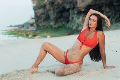 Sexy brunette girl in red swimsuit lies and sunbathes on beach with rocks. Sexy brunette girl in red swimwear lies and sunbathes on beach with rocks. Beautiful stock photo