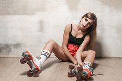 Sexy brunette girl sitting on the floor in roller skating. Royalty Free Stock Images