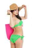 Sexy brunette girl wearing green swimsuit and big hat Stock Image