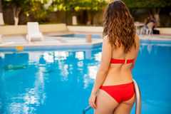 Sexy brunette going inside a pool Stock Images