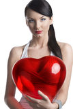Sexy brunette with heart shaped balloon looks in to the lens Royalty Free Stock Photos