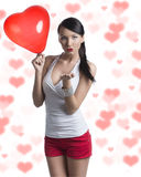 Sexy brunette with heart shaped balloon sends a kiss Stock Image