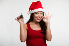 Sexy brunette holding a car key, wearing santa hat Stock Photos