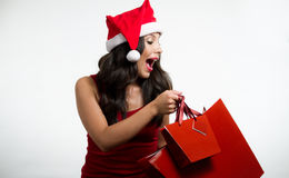 Sexy brunette holding Christmas red shopping bags Royalty Free Stock Photos