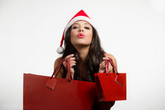 Sexy brunette holding Christmas red shopping bags Royalty Free Stock Photography