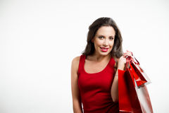 Sexy brunette holding red shopping bags Royalty Free Stock Photo