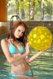 brunette holding a yellow poka dot beach ball Stock Photo