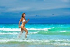 Sexy Brunette läuft auf den Wellen in einem stilvollen weißen Bikini Lizenzfreies Stockfoto