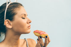 Sexy brunette lady eat sweet heart shaped donut. Royalty Free Stock Image
