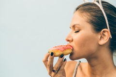 brunette lady eat sweet heart shaped donut. Stock Photos