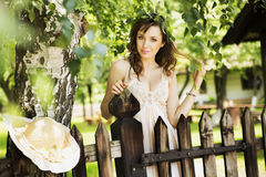 Sexy brunette lady leaning on the wooden fence Royalty Free Stock Photos
