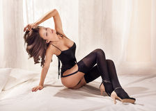 Sexy brunette lady posing in bed Stock Photography