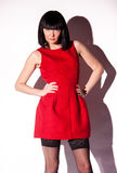 Sexy brunette lady in short red dress and black stockings Royalty Free Stock Photo