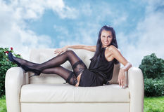 Sexy brunette laying on a couch wink in black dress. On a garden background Royalty Free Stock Photography