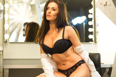 Sexy brunette in lingerie and black shoes sitting on the visage' Royalty Free Stock Photography