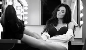 Sexy brunette in lingerie and black shoes sitting on the visage` Stock Image