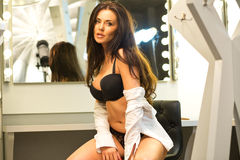 Sexy brunette in lingerie and black shoes sitting on the visage' Stock Photos