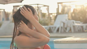 Brunette with long hair dressed in a pink. Brunette with long hair dressed in pink bikini pours herself with water in swimming pool stock video