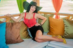 Sexy brunette in the gazebo with cushions. Sexy brunette with long hair and red top on the sofa with cushions in the gazebo Royalty Free Stock Photography