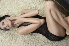 Sexy brunette lying on carpet on the her back Stock Photos
