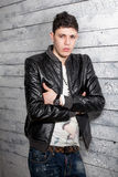 Sexy brunette man in leather coat leaning against wooden wall Royalty Free Stock Image