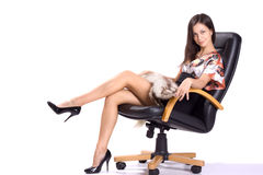 Sexy brunette in mini with fur seat on armchair Stock Image